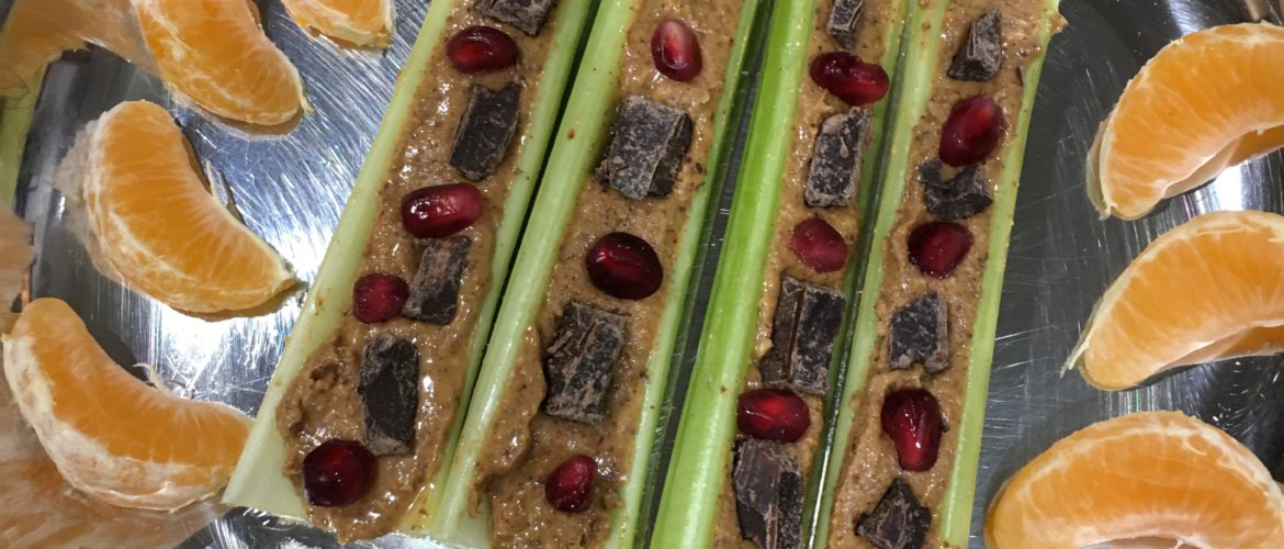 Celery with almond butter, dark chocolate and pomegranate seeds and clementine